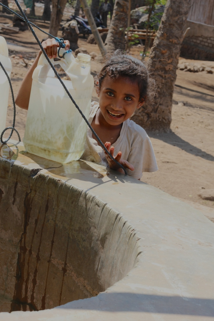 Little girl on Lembata drawing water from the village well